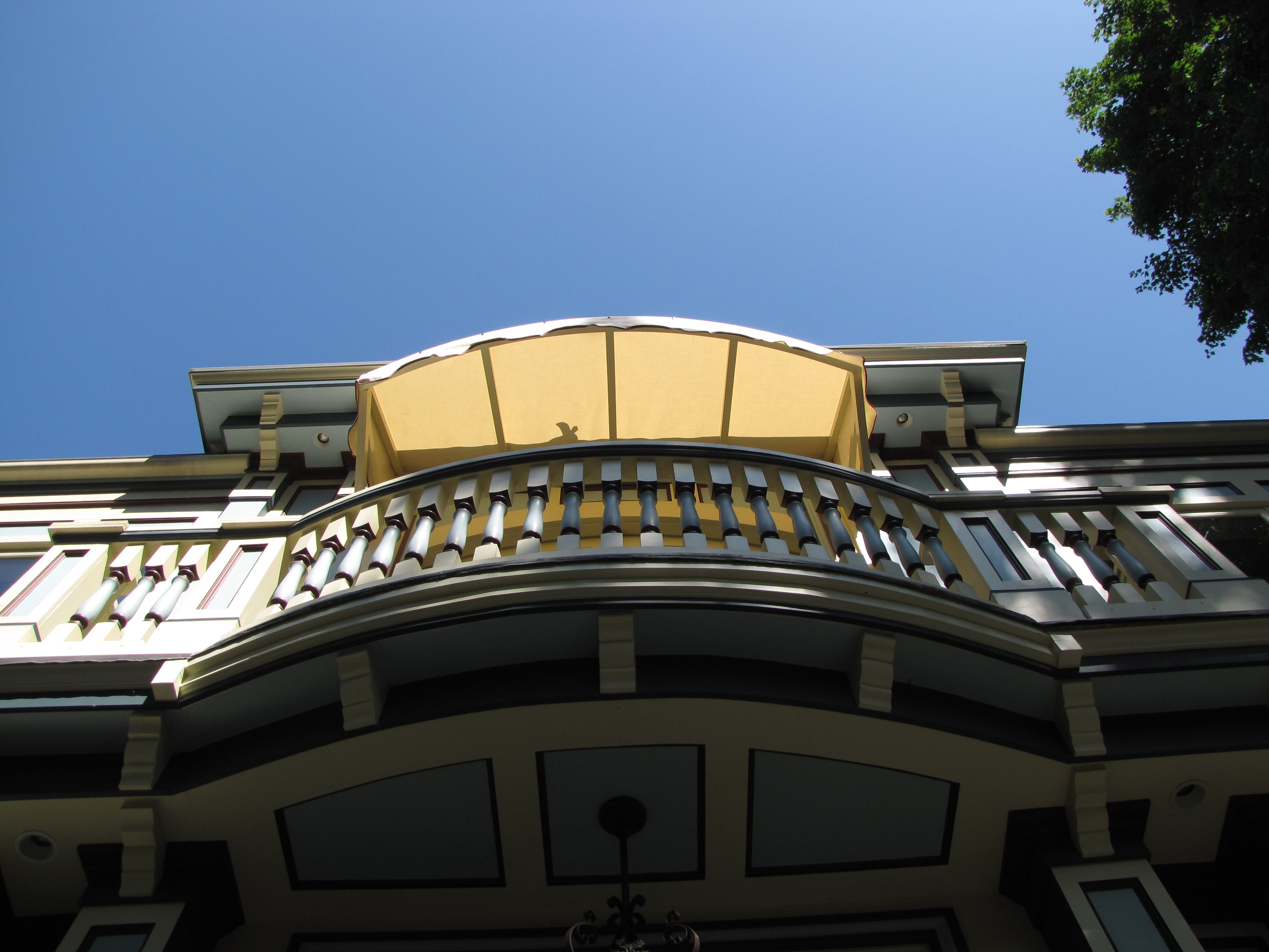 This wood framed awning covers an elegant balcony space.